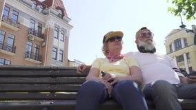 Παππούδες και γιαγιάδες στα σύγχρονα ενδύματα και εξαρτήματα που χαλαρώνουν στον πάγκο στην πόλη φιλμ μικρού μήκους