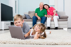 Παππούς και γιαγιά που εξετάζει τα εγγόνια τους που χρησιμοποιούν το lap-top Στοκ Εικόνες