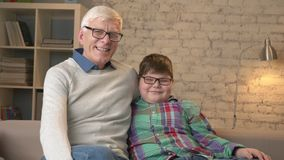 Παππούς και εγγονός με τα γυαλιά, καθμένος στον καναπέ, χαμογελώντας και εξετάζοντας τη κάμερα Εγχώρια άνεση, οικογένεια απόθεμα βίντεο