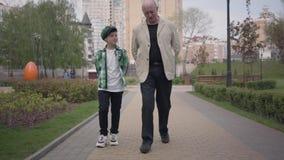 Παππούς και εγγονός πορτρέτου που περπατούν στη κάμερα στο πάρκο Έννοια γενεών r Ελεύθερος χρόνος υπαίθρια απόθεμα βίντεο