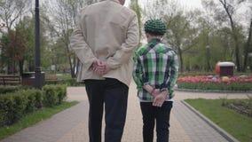 Παππούς και εγγονός πορτρέτου που περπατούν στο πάρκο με τις πλάτες τους στη κάμερα Και οι δύο άνθρωποι έχουν τα χέρια τους πίσω απόθεμα βίντεο