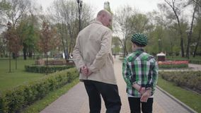 Παππούς και εγγονός που περπατούν στο πάρκο με τις πλάτες τους στη κάμερα Και οι δύο άνθρωποι έχουν τα χέρια τους πίσω από τις πλ απόθεμα βίντεο