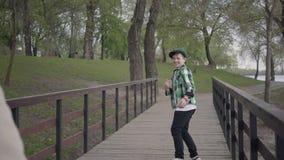 Παππούς και εγγονός που περπατούν στο πάρκο σε μια γέφυρα Το παιδί αρχίζει και το άτομο για να τον ενώσει _ απόθεμα βίντεο