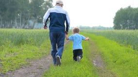 Παππούς και εγγονός που τρέχουν στην επαρχία απόθεμα βίντεο