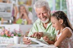 Παππούς με την εγγονή που χρησιμοποιεί το lap-top Στοκ φωτογραφία με δικαίωμα ελεύθερης χρήσης