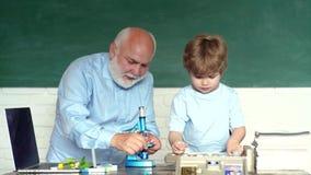 Παππούς με την εκμάθηση εγγονών από κοινού Έννοια εκμάθησης και εκπαίδευσης u Δημοτικό σχολείο και απόθεμα βίντεο