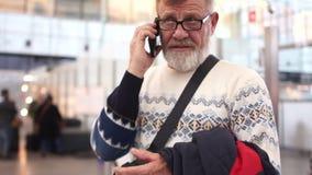 Παππούς με την κινητή τηλεφωνική διαθέσιμη ομιλία στον αερολιμένα Το άτομο είναι αυστηρό και σοβαρό απόθεμα βίντεο
