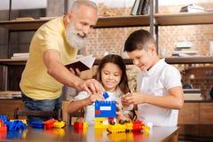 Παππούς που βοηθά τα εγγόνια να χτίσουν έναν πύργο με το σύνολο κατασκευής Στοκ Εικόνες