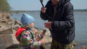 Παππούς που δίνει ένα πιασμένο ψάρι στο εγγόνι απόθεμα βίντεο