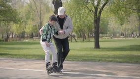 Παππούς που διδάσκει τον εγγονό του για να οδηγήσει τα σαλάχια κυλίνδρων στο πάρκο Το παλαιό χέρι εκμετάλλευσης ατόμων του αγοριο φιλμ μικρού μήκους