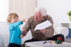 Παππούς που διπλώνει το αεροπλάνο Στοκ Εικόνες
