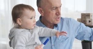 Παππούς που μιλά με την εγγονή μωρών στο σπίτι απόθεμα βίντεο
