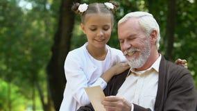 Παππούς που παρουσιάζει εικόνα στην εγγονή και που λέει την ενδιαφέρουσα ιστορία απόθεμα βίντεο