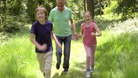 Παππούς που χαράζει τα εγγόνια κατά μήκος της δασόβιας πορείας φιλμ μικρού μήκους