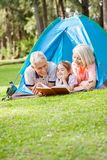 Παππούδες και γιαγιάδες που διαβάζουν το βιβλίο για την εγγονή Στοκ Εικόνες