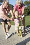 Παππούδες και γιαγιάδες που διδάσκουν την εγγονή για να οδηγήσει το μηχανικό δίκυκλο στο πάρκο Στοκ εικόνες με δικαίωμα ελεύθερης χρήσης