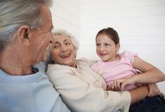 Παππούδες και γιαγιάδες που κάθονται με την εγγονή στον καναπέ Στοκ Φωτογραφίες