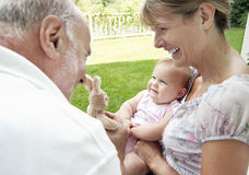 Παππούδες και γιαγιάδες που παίζουν με την εγγονή Στοκ Φωτογραφία
