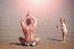Παράδειγμα γονέα γιόγκα για όλους πατέρας και παιδί που κάνουν τις ασκήσεις γιόγκας στην παραλία Στοκ Φωτογραφίες