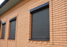 Παράθυρα σπιτιών με τα κυλώντας παραθυρόφυλλα για την εγχώρια προστασία στοκ φωτογραφία