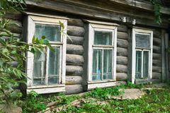 Παράθυρα του παλαιού ξεχαρβαλωμένου σπιτιού εισδύοντος στη γη σε μια μικρή ρωσική πόλη στοκ φωτογραφίες