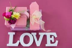 Παράθυρα δώρων με τα λουλούδια και αγάπη κειμένου στο ρόδινο κλίμα Στοκ φωτογραφία με δικαίωμα ελεύθερης χρήσης