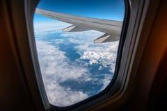 Παράθυρο αεροπλάνων από μέσα Μέσω του παραθύρου μπορείτε να δείτε τα σύννεφα και το φτερό αεροπλάνων Στοκ Εικόνες