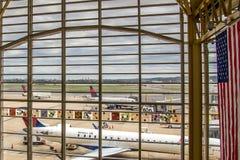 Παράθυρο αερολιμένων άποψης έξω στα αεροπλάνα και τις διαδικασίες κεκλιμένων ραμπών Στοκ Φωτογραφία