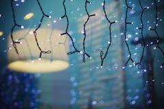 Παράθυρο γιρλαντών Χριστουγέννων και καφέδων φω'των στην αντανάκλαση Στοκ φωτογραφία με δικαίωμα ελεύθερης χρήσης
