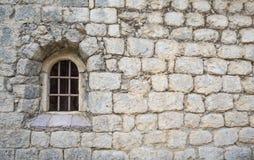 Παράθυρο με έναν φραγμό στην παλαιά εκκλησία τεχνητός μπλε ελαφρύς τοίχος πετρών Στοκ Εικόνα