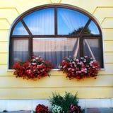 Παράθυρο που διακοσμείται με δύο καλάθια των κόκκινων λουλουδιών Στοκ εικόνες με δικαίωμα ελεύθερης χρήσης