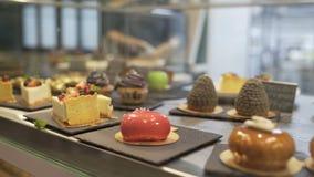 Παράθυρο του καταστήματος κέικ με την ποικιλία των κέικ στην επίδειξη Κατάστημα ζύμης με muffins, eclaire, κέικ με τα φρούτα, μού φιλμ μικρού μήκους