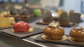 Παράθυρο του καταστήματος κέικ με την ποικιλία των κέικ στην επίδειξη Κατάστημα ζύμης με muffins, eclaire, κέικ με τα φρούτα, μού απόθεμα βίντεο