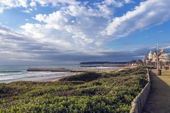 Παράκτια θάλασσα παραλιών βλάστησης αμμόλοφων τοπίων ενάντια στην πόλη Skylin Στοκ Εικόνες