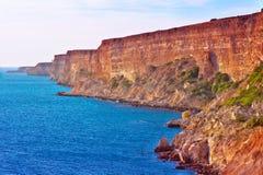 Παράκτιοι κόκκινοι βράχοι και μπλε ταξίδι τοπίων θάλασσας θερινό Στοκ φωτογραφίες με δικαίωμα ελεύθερης χρήσης