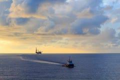Παράκτιος γρύλος επάνω στην εγκατάσταση γεώτρησης διατρήσεων και τη βάρκα ανεφοδιασμού Στοκ Εικόνα