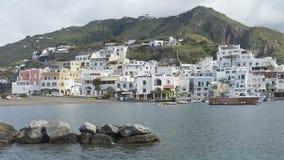 Παράκτιος χτισμένος Λευκοί Οίκοι ανήφορος που απασχολεί το μικρό κόλπο, νησί ισχίων στην Ιταλία απόθεμα βίντεο