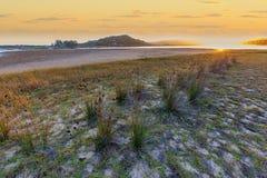 Παράκτιο ηλιοβασίλεμα εκβολών με την παραλία χλόης στοκ εικόνα με δικαίωμα ελεύθερης χρήσης