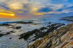 Παράκτιο ηλιοβασίλεμα και θάλασσα με τους βράχους και τα σύννεφα στοκ εικόνα με δικαίωμα ελεύθερης χρήσης