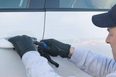 Παράνομο άνοιγμα μιας πόρτας αυτοκινήτων από ένα άτομο στα μαύρα γάντια στοκ φωτογραφία με δικαίωμα ελεύθερης χρήσης