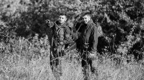 Παράνομο κυνήγι Οι φίλοι κυνηγών απολαμβάνουν τον ελεύθερο χρόνο Κυνηγοί με τα τουφέκια στο περιβάλλον φύσης Συνεργάτης λαθροκυνη στοκ εικόνες με δικαίωμα ελεύθερης χρήσης