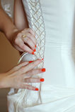 Παράνυμφοι που βοηθούν τη νύφη για να φορέσει ένα γαμήλιο φόρεμα στοκ φωτογραφία