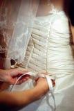 Παράνυμφοι που βοηθούν τη νύφη για να φορέσει ένα γαμήλιο φόρεμα στοκ εικόνες