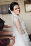 Παράνυμφοι την όμορφη νύφη brunette που τίθεται που βοηθούν στο γάμο dres Στοκ Φωτογραφία