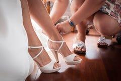 Βοήθεια να φορεθεί η νύφη τα παπούτσια στοκ εικόνες