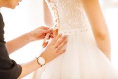 Παράνυμφος που βοηθά τη νύφη για να βάλει το γαμήλιο φόρεμά της επάνω Στοκ Εικόνα