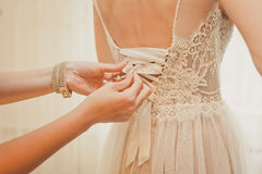 Παράνυμφος που κουμπώνει το φόρεμα στη νύφη Στοκ Εικόνες