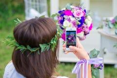 Παράνυμφος που φωτογραφίζει μια γαμήλια ανθοδέσμη στο τηλέφωνο ανθοκόμος Στοκ φωτογραφίες με δικαίωμα ελεύθερης χρήσης