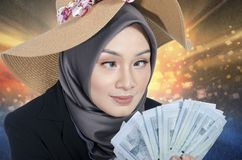 Παράξενη έκφραση από τη νέα γυναίκα κρατώντας το τραπεζογραμμάτιο πέρα από το αφηρημένο υπόβαθρο Στοκ εικόνα με δικαίωμα ελεύθερης χρήσης