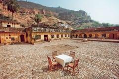 Παράξενο εστιατόριο υπαίθριο στο αρχαίο ινδικό προαύλιο σπιτιών Κενός πίνακας με τους ανθρώπους τραπεζομάντιλων και καρεκλών whit Στοκ Εικόνα